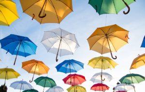 上空で開いた傘が大量に浮かんでいる写真