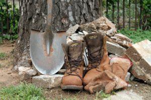 大木の根元に置かれているシャベルとブーツ