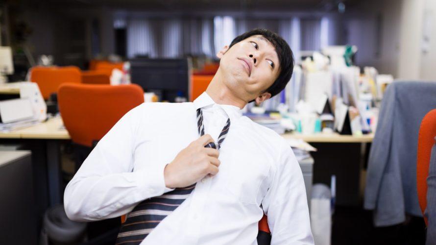 オフィスにて疲れた様子でネクタイを緩めるサラリーマン