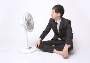 扇風機で涼んでいるスーツ姿の男性