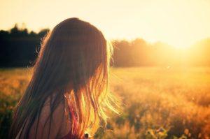 夕焼けの草原に佇む女性